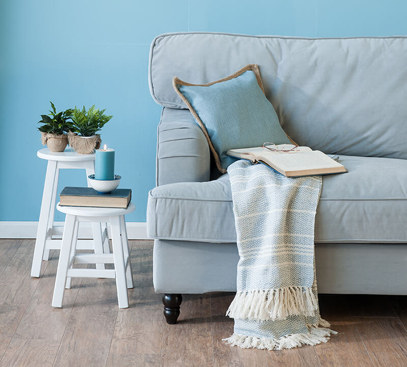 comfy blue couch with blanket and book